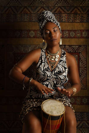 Black African American woman in African clothing and ethnic head wrap plays the tambourine in studio