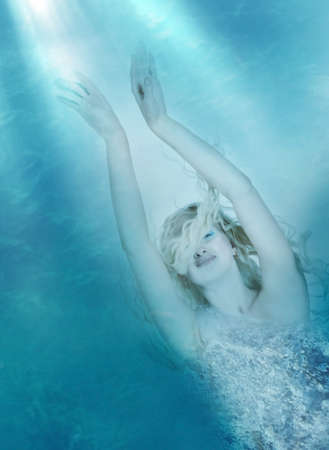 Concept photograph of a young blond woman floating in the depths of a blue ocean