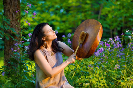 Female shaman playing on shaman frame drum at dawn in the forest on background with leaves and flowers