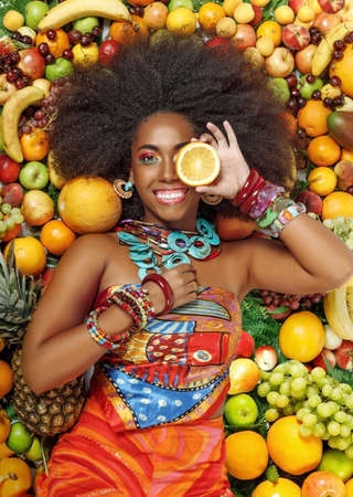 Young beautiful African American Black woman with afro hairstyle smiles closing one eye with a slice of orange while lying among fruits in the studio