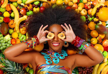 Young beautiful African American Black woman with afro hairstyle smiles closing her eyes with apricots while lying among fruits in the studio