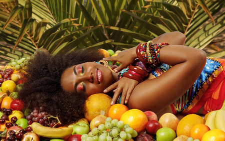Young lovely African American Black woman smiling with closed eyes while lying among fruits on a background of palm leaves
