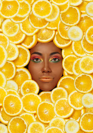 Portrait of a young beautiful African American Black woman against the background of sliced orange Foto de archivo