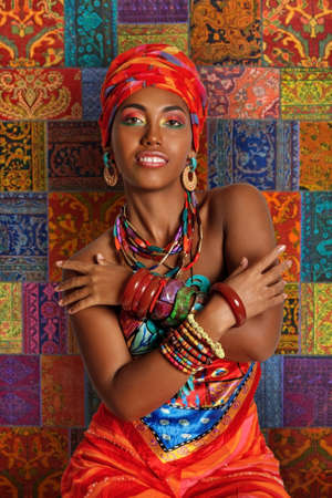 Portrait of a young and attractive African American black woman in the national African clothes against the background of a traditional African carpet