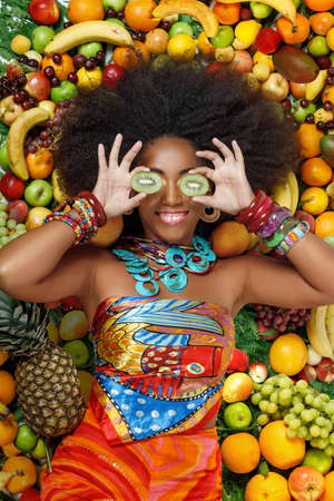 Young beautiful African American Black woman with afro hairstyle smiles closing her eyes with kiwi fruit while lying among fruits in the studio