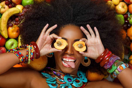 Portrait of a young beautiful African American Black woman with afro hairstyle smiles closing her eyes with apricots while lying among fruits in the studio