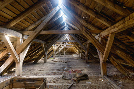 The attic of an old ruined house, light shines through holes in the roof Banque d'images