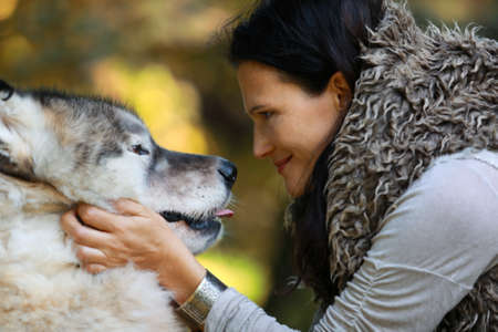 Portrait of a woman with an Alaskan Malamute dog in the forest against the background of nature