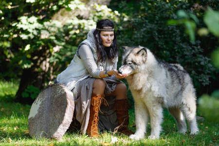 Shaman woman feeding her big Alaskan Malamute dog in the forest