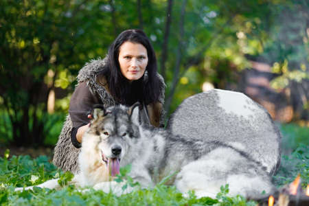 Portrait of a shaman woman with an Alaskan Malamute dog next to the fire in the forest