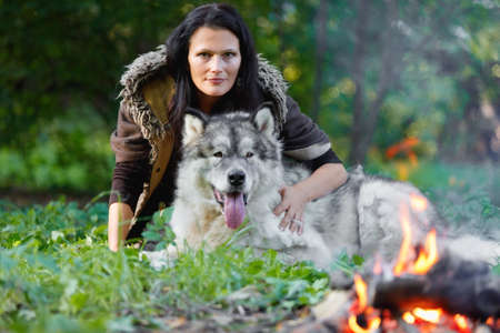 Portrait of a pretty woman with an Alaskan Malamute dog by the fire against the background of nature