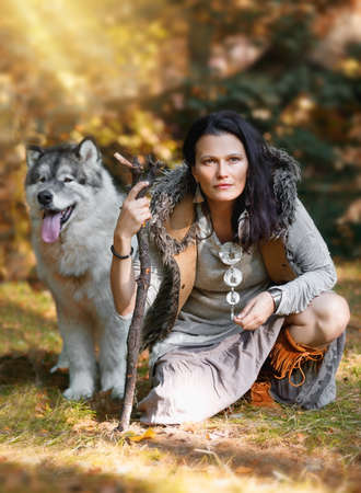 Portrait of a forest dweller woman with a large dog Alaskan Malamute in the autumn forest