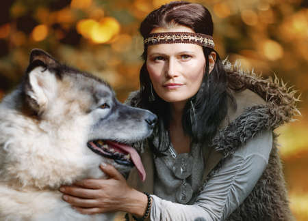 Portrait of a pretty woman with an Alaskan Malamute dog in the forest against the background of nature