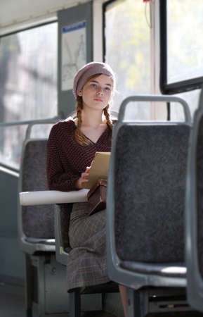 Dreamy girl in retro style clothes rides on public transport Imagens