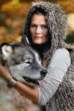 Portrait of a young nice woman with an Alaskan Malamute dog in the autumn forest against the background of nature