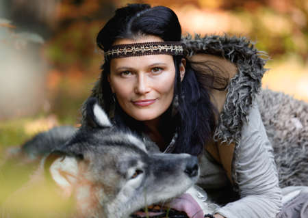 Portrait of a nice woman with an Alaskan Malamute dog in the autumn forest against the background of nature