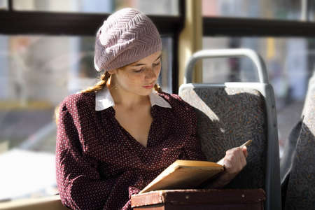 Young attractive student girl in retro style clothes reads a book in a moving tram
