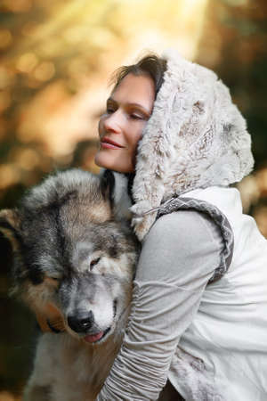 Portrait of a young likable woman with an Alaskan Malamute dog in the autumn forest against the background of nature Фото со стока