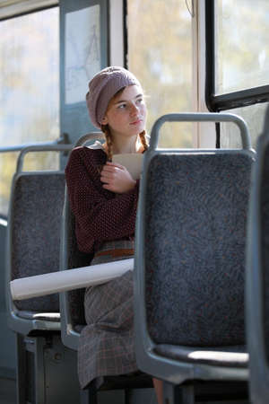 Dreamy girl in retro style clothes rides in an empty tram on a summer day