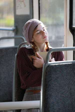 Charming girl in retro style clothes rides in an empty city tram on a summer day