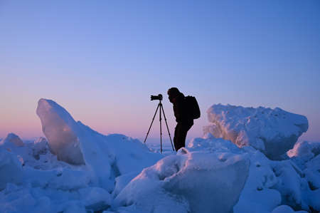 Photographer with a tripod shoots a sunset among the snow-covered hummocks of Lake Baikal on a cold February evening, Russia.