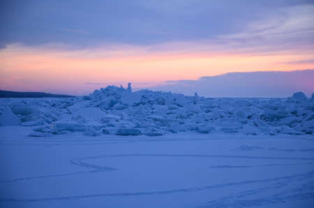 Amazing sunset sky and ice on Lake Baikal. Natural breaking ice over frozen water lake Baikal in Russia at winter season, landscape background