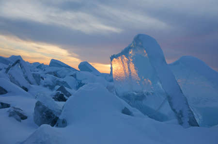 Amazing sunset sky and ice on Lake Baikal in Russia. Natural breaking ice over frozen water lake at winter season, landscape background