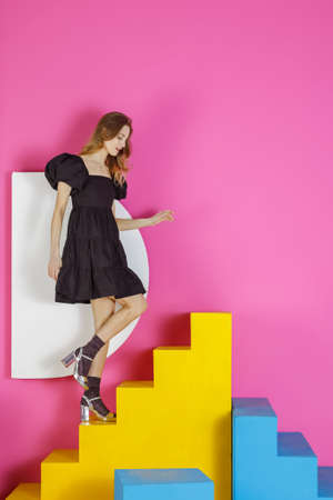 Young pleasing woman in a black dress poses in a studio sitting on colored stairs against a pink wall