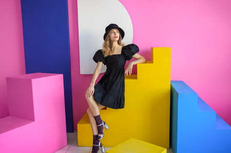 Young pleasing woman in a black hat and dress poses in a studio sitting on colored stairs against a pink wall