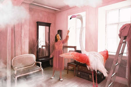 Young woman holds out a branch to a pink flamingo in a sun drenched vintage style living room Zdjęcie Seryjne