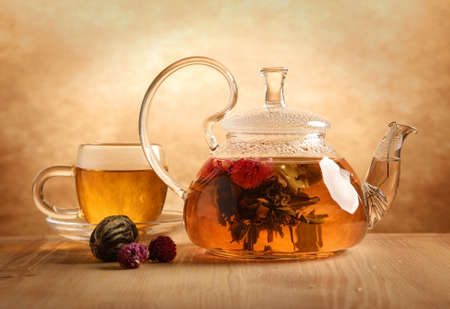 Glass tea teapot with a blooming tea flower stands on the table indoors