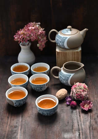 Studio photo of a tea set with tea poured into cups over dark background Zdjęcie Seryjne