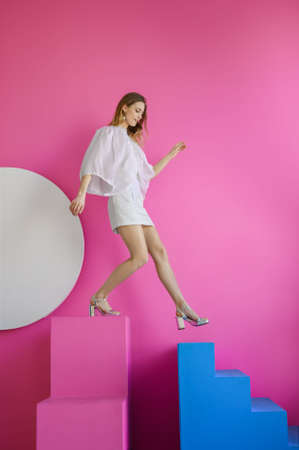 Young adult woman in white dress standing on the stairs on pink background