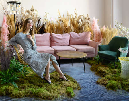 Fantasy concept with a young woman posing in a room in the middle of tall grass with the floor flooded with water Zdjęcie Seryjne