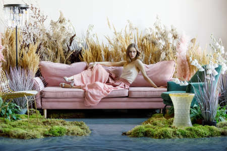 Fantasy concept with a young woman sitting on a sofa in a room in the middle of tall grass with the floor flooded with water Zdjęcie Seryjne