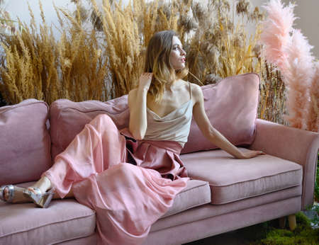 Young adult woman sitting on a sofa in a room in the middle of tall grass