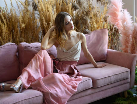 Nice woman sitting on a sofa in a room in the middle of tall grass Zdjęcie Seryjne