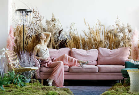 Fantasy concept with a nice woman posing in a room in the middle of tall grass with the floor flooded with water Zdjęcie Seryjne