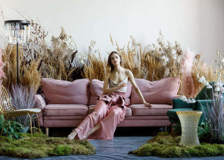 Fantasy concept with pleasant woman posing in a room in the middle of tall grass with the floor flooded with water