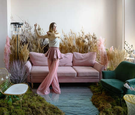 Beauty young woman dancing in a room with sofa in the middle of tall grass with the floor flooded with water Zdjęcie Seryjne