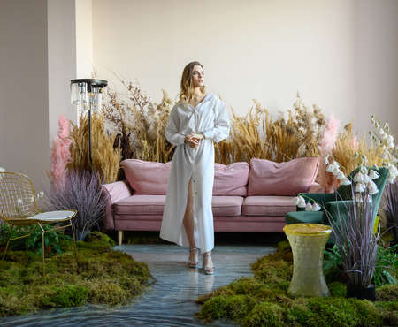 Pleasant young woman walks on a water filled floor in a room with sofa in the middle of tall grass