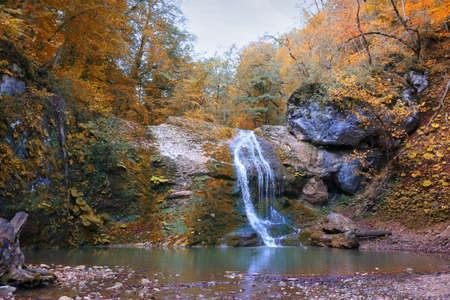 Beautiful waterfall with a mountain pond in the autumn forest in Adygea Republic, Russia