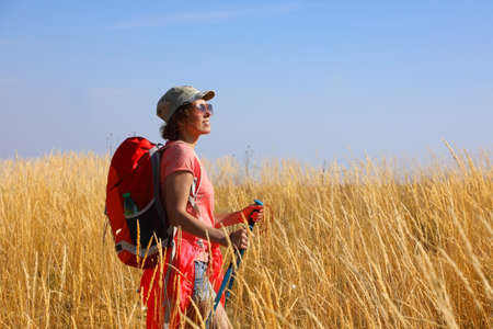 Female tourist with a backpack and Nordic walking sticks walking through a field of yellow grass in the boundless steppes of the golden autumn wilderness