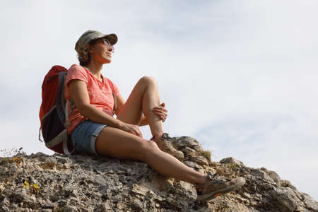 Female tourist with backpack on top of a hill in silence and loneliness admires a tranquil natural landscape in search of a soul