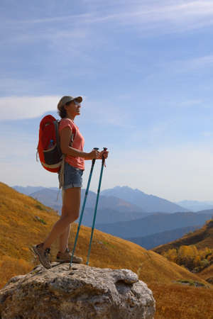 Female tourist with backpack stands on the top of a mountain and admires the beautiful views of the mountains on a sunny autumn day