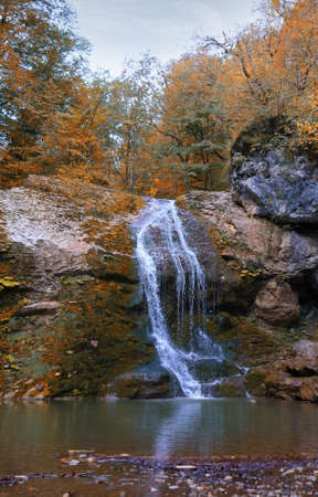 Beautiful waterfall with a pond in the autumn mountains in Adygea Republic, Russia Zdjęcie Seryjne