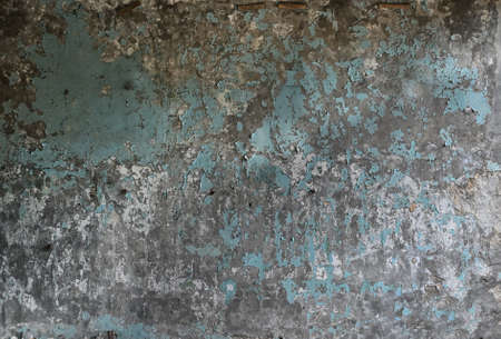 The texture of an old wall with peeling paint of an old abandoned industrial building, close-up
