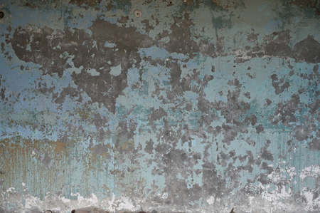 Texture of an old wall with peeling paint of an old abandoned industrial building, close-up