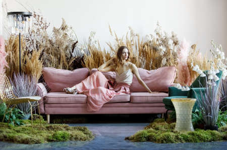 Fantasy concept with young sweet woman posing in a room in the middle of tall grass with the floor flooded with water