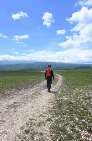 A lone male tourist walks along a dirt road in a mountainous area Zdjęcie Seryjne